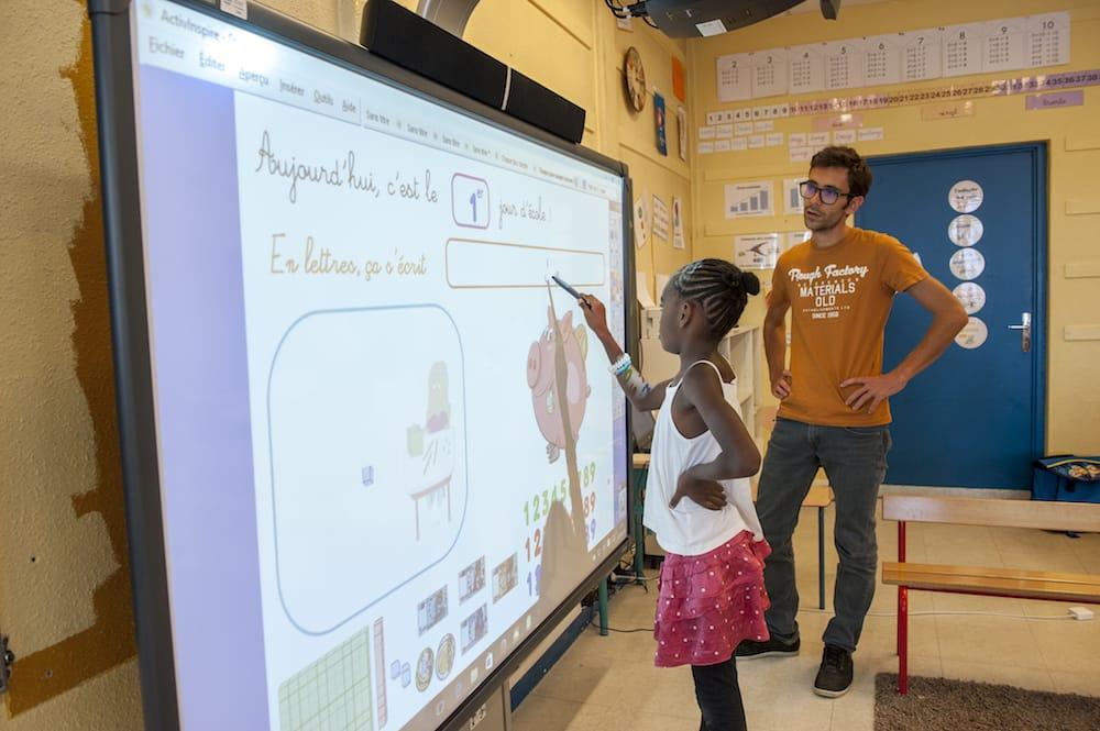 Élève et professeur devant un tableau numérique