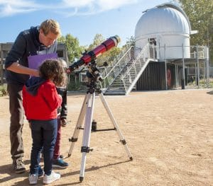 Enfants et animateur devant un téléscope