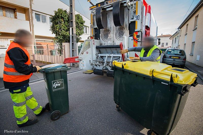 Des éboueurs vident des bacs à poubelle